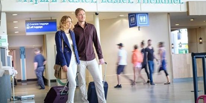 Couple walking in airport with suitcases